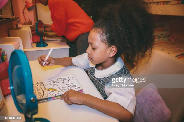 Afrolatina girl in plaid uniform sitting at desk. Girl is holding a marker and coloring in a book. Blue mirrors on two desks. Afrolatina mom in partial view. Background is a bedroom.