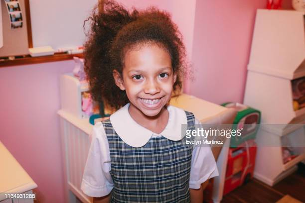 Afrolatina girl looking at camera, smiling. Background is a desk, dry erase board and storage containers in a pink bedroom.