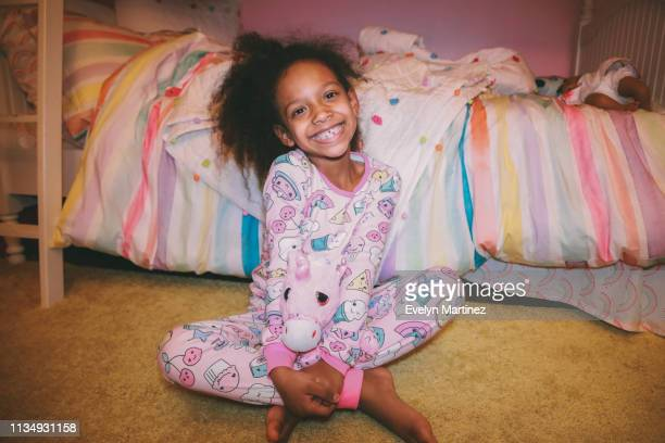 Afrolatina girl sitting on yellow carpet holding a stuff unicorn, smiling at the camera. Colorful bed and pink wall in the background of bedroom.