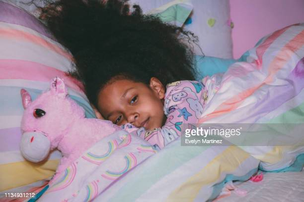 afrolatina girl tucked into colorful bed comforter, girl looking away. pillows and a stuffed unicorn in frame. pink wall in the background - evelyn martinez stock pictures, royalty-free photos & images