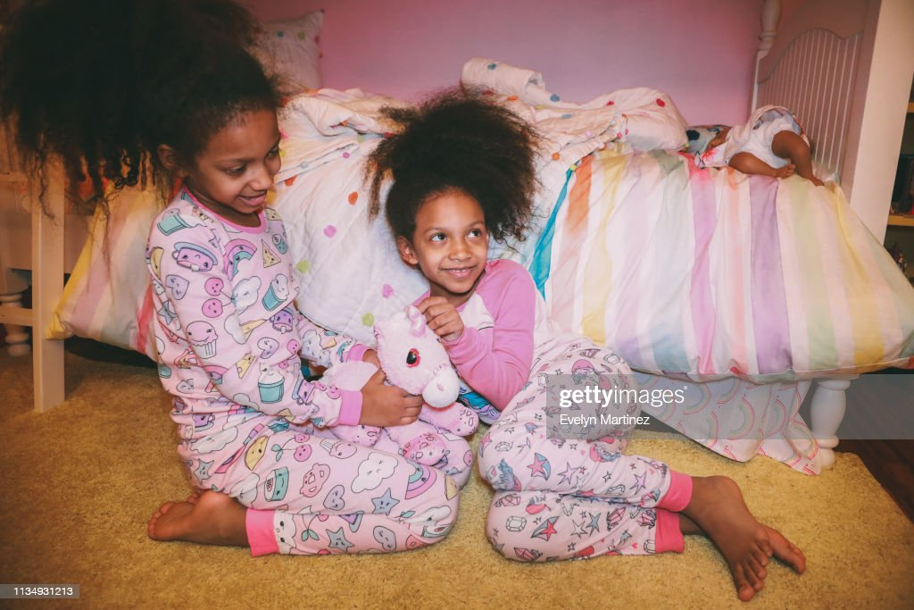 Afrolatina Identical Twins sitting on a yellow carpet, looking away from the camera. Both twins are in pajamas. One twin is looking up and smiling. : Stock Photo