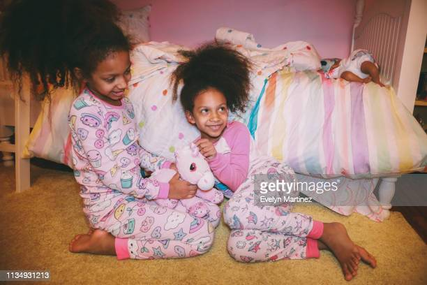 Afrolatina Identical Twins sitting on a yellow carpet, looking away from the camera. Both twins are in pajamas. One twin is looking up and smiling.