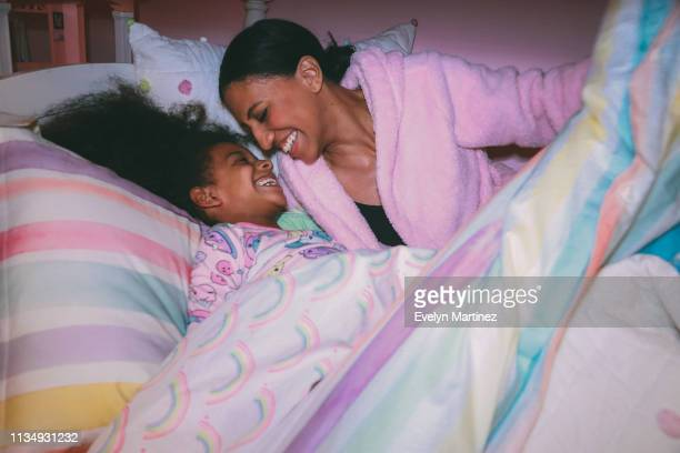 Afrolatina Mom and Afrolatina daughter laughing, tucked into bed comforter. Daughter is wearing pajamas. Mother is wearing a pink robe.