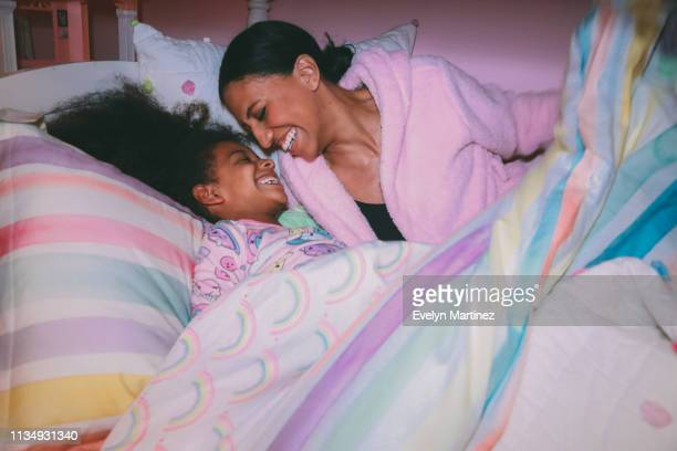 afrolatina mom and afrolatina daughter laughing, tucked into bed comforter. daughter is wearing pajamas. mother is wearing a pink robe. - evelyn martinez stock pictures, royalty-free photos & images