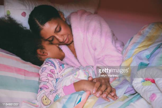 Afrolatina Mom and Daughter with eyes closed, tucked into bed comforter, out of focus. Hands and pajamas in focus.