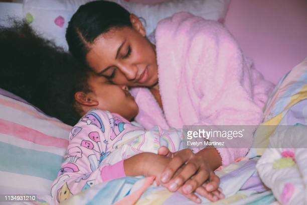 afrolatina mom and daughter with eyes closed, tucked into bed comforter, out of focus. hands and pajamas in focus. - evelyn martinez stock pictures, royalty-free photos & images