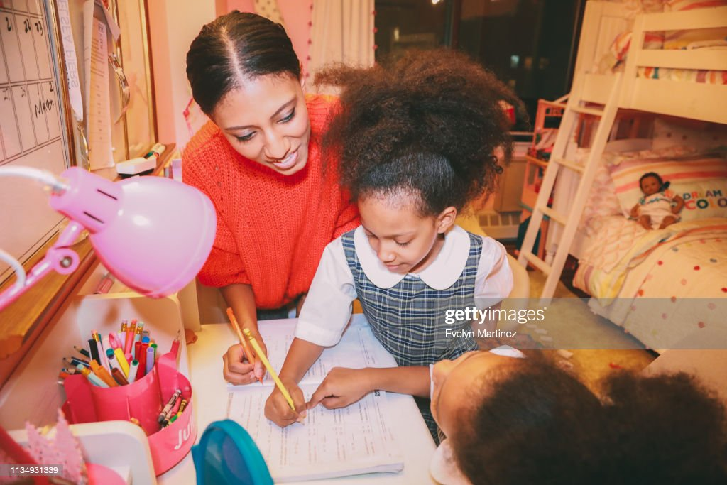 Afrolatina mom and twin daughters doing homework at home. Daughters are in their school uniform. Background is a pink bedroom. : Stock Photo