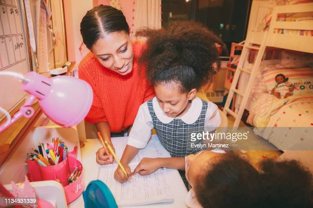 Afrolatina mom and twin daughters doing homework at home. Daughters are in their school uniform. Background is a pink bedroom.