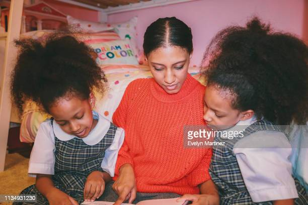 Afrolatina Mom and Twin Daughters looking down at book. Mom and daughters looking away from the camera. Twins are wearing school uniform. Dream in Color pillow and dollhouse in the background of the photo.