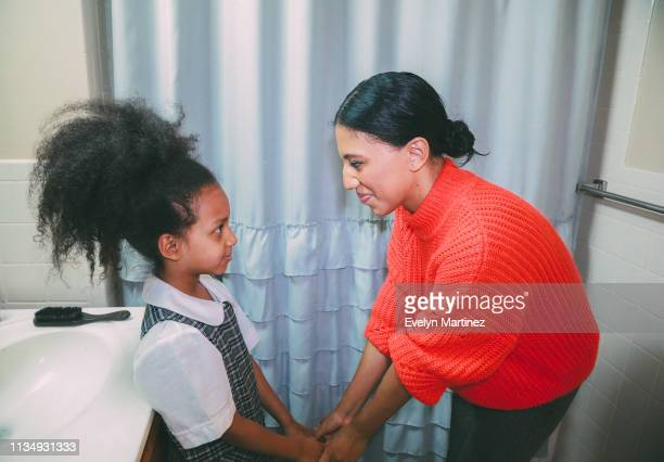 afrolatina mom holding afrolatina daughter's hands while they look into each others eyes. background is a bathroom with a white sink. hair comb in the corner. - evelyn martinez stock pictures, royalty-free photos & images