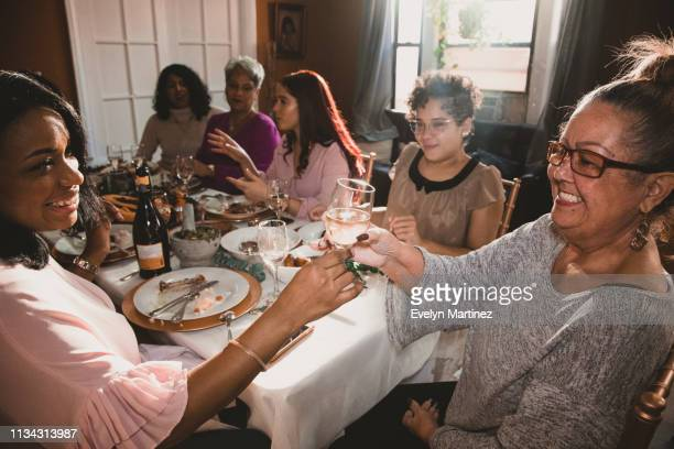 afrolatina mom is passing a glass of prosecco to grandmother. model in short wavy hair with beige and black top smiling at them. background is a dinner party in a living room. - nosotroscollection stock pictures, royalty-free photos & images