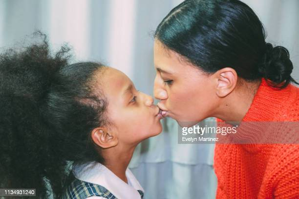 Afrolatina mom kissing Afrolatina daughter on the lips. Mom is wearing hair in a bun. Daughter has her afro in a ponytail and is wearing school uniform.