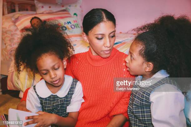 afrolatina mom reading to twin daughters. mom is looking over at twin on the right side of the photo. other twin is flipping through pages of the book. - evelyn martinez stock pictures, royalty-free photos & images