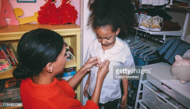 afrolatina mom with afrolatina daughter, by bedroom closet. mom and daughter looking away from camera, mom has her hands on the buttons of daughter's white shirt. - evelyn martinez stock pictures, royalty-free photos & images