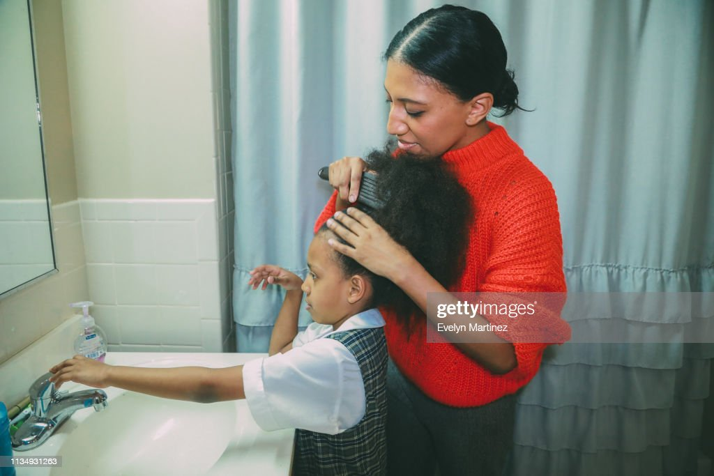 Afrolatina mom with Afrolatina daughter in the bathroom. Mom is combing daughter's afro. Daughter reaches out for faucet handle. : Stock Photo