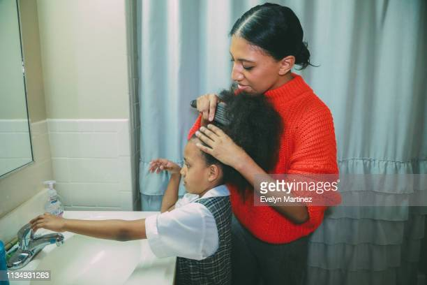 Afrolatina mom with Afrolatina daughter in the bathroom. Mom is combing daughter's afro. Daughter reaches out for faucet handle.