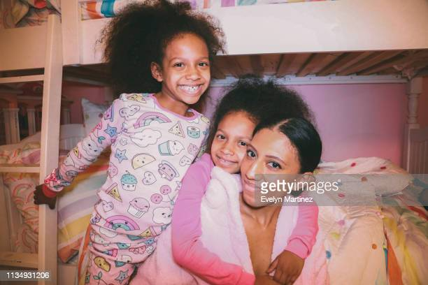Afrolatina Twin Daughter embracing Afrolatina Mom from behind. Second daughter smiling and holding onto bunk bed staircase.