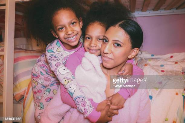 Afrolatina Twin Daughters and Mom embracing, all looking at the camera and wearing pajamas/sleepwear.