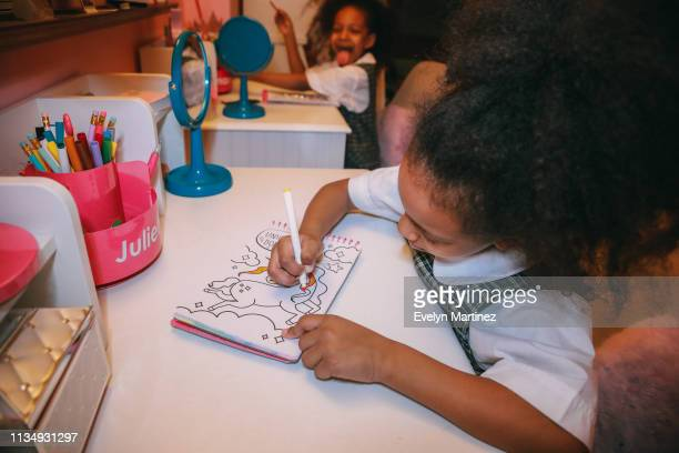 Afrolatina twin girl coloring at her desk. Twin in the background sticking out tongue and smiling. Pencils and desk accessories in the frame.