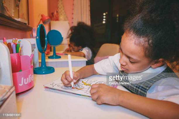 Afrolatina twin sisters sitting at desk coloring. Blue mirrors and pink accessories in the frame. Bedroom window in the background.
