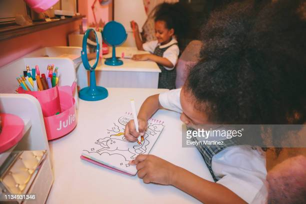 Afrolatina twins at desks coloring. Twins are wearing plaid school uniforms. Background is a pink bedroom.