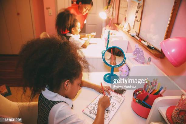 Afrolatina twins coloring at their desks. Mom and other twin out of focus in the background. Closet and bedroom door visible.