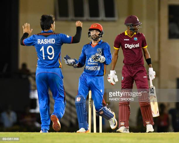 Afsar Khan Zazai and Rashid Khan Arman of Afghanistan celebrate the dismissal of Roston Chase of West Indies during the 2nd ODI match between West...