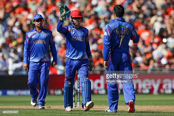 Afsar Zazai of Afghanistan congratulates teammate Mohammad Nabi after taking the wicket of Brendon McCullum of New Zealand during the 2015 ICC...