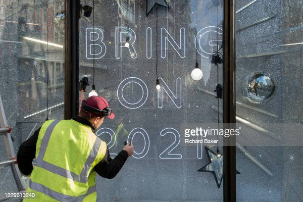 After a bleak year of Coronavirus pandemic misery, a contractor applies stars to window glass in Harvey Nichols's Christmas-themed window which urges...