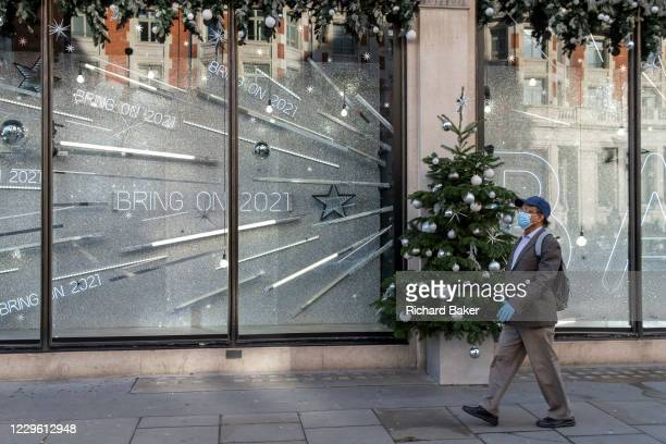 After a bleak year of Coronavirus pandemic misery, a shopper wearing a face mask and gloves walks past the temporary Christmas-themed Harvey Nichols...