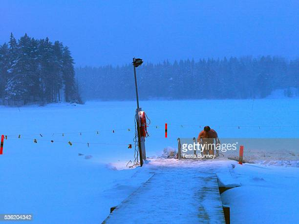 After a brief dip a man gets out the hole cut into a frozen lake for iceswimming Kallavesi Kuopio Central Finland Ice swimming takes place in a body...