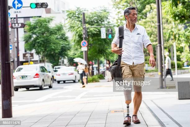 Na een drukke dag in Osaka, man Japans dragen prothetische been lopen terug naar huis