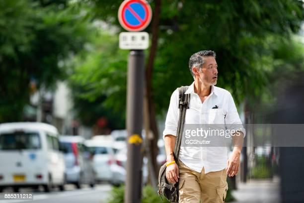 忙しい一日の後ハンサムな日本人男の家から歩いて戻って - もがく ストックフォトと画像