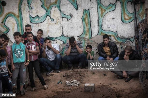 After a funeral, Palestinians gather to mourn in a cemetary close to the tomb of a 23 year old Palestinian who was killed earlier this day by Israeli...