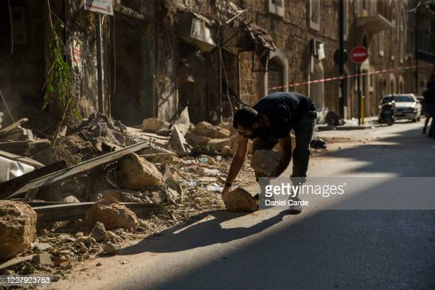 After a massive explosion shook the city a day before, a man gathers rubble that fell when a building was damaged by the explosion on Aug. 5, 2020 in...