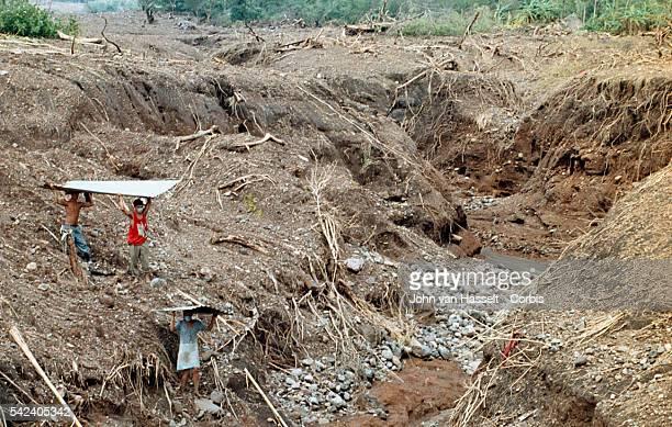 After a mudslide destroyed their village on the Casitas volcano surivors collect scrap iron