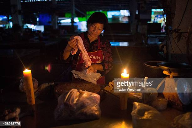 After a power outage a vendor lights candles and continues to sell meat on November 7 2014 in Ban Tha Rae Thailand The Tha Rae market was well known...