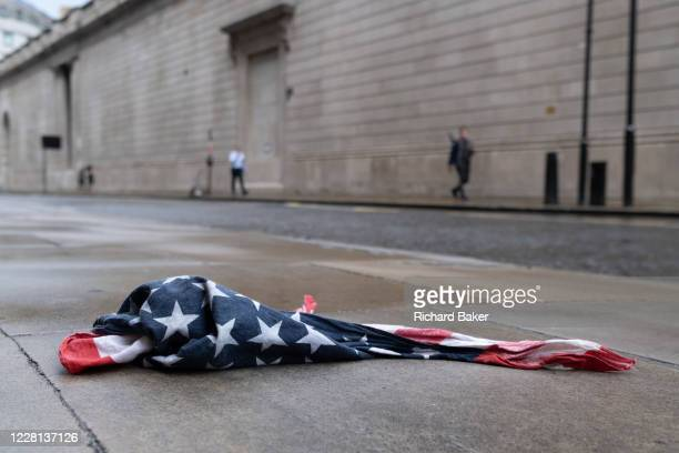 After a rain shower, an American Stars and Stripes flag bandana lies on the wet pavement opposite the high wouter wall of the Bank of England in the...