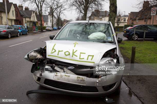 After a recent car crash a smashed Ford Fiesta with activated airbags is parked on the side of the road awaiting recovery with the word Broken...