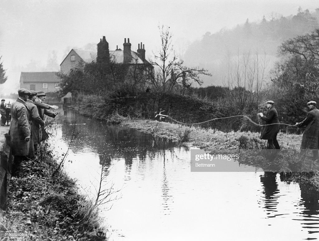 After a search in which Scotland Yard was baffled, and folk throughout the countryside turned out to do their bit, Mrs. Agatha Christie, the noted writer who mysteriously disappeared from her home, was found, merely by accident, at a small hotel. Her abandoned auto was found, in the search which led to the dragging of a neary-by pond. This photo shows men doing the latter in the vicinity of Newlands Corner, Surrey. | Location: Newlands Corner, Surrey, England, UK.