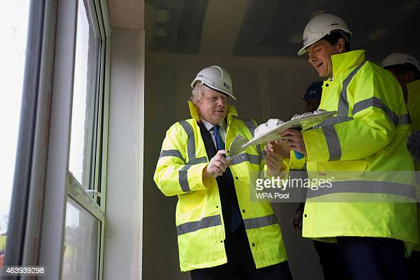 After a short demonstration on plastering Britain's Chancellor of the Exchequer George Osborne and London Mayor Boris Johnson make an attempt to...