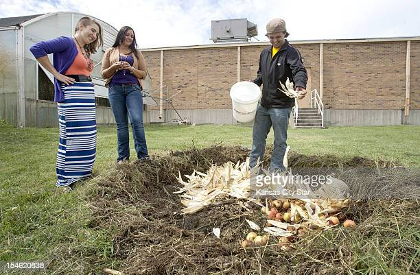 After a small harvest Jessica Lackey from left Kelda Britton watch as Brett Ramey adds cornhusks to the contents in a circular compost pit at Haskell...