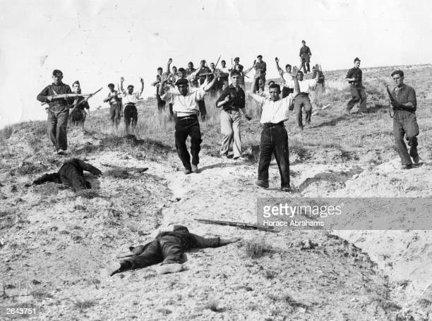 After a successful attack, Nationalist troops capture communist troops entrenched on the crest of a hill on the Somosierra front, during the Spanish...