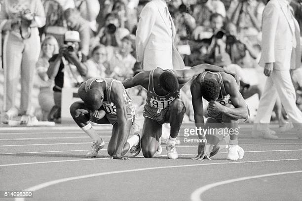 After a three-medal, 200-meter race at the 1984 Olympics, Thomas Jefferson , Carl Lewis, and Kirk Baptiste pause on the track for a prayer of thanks.
