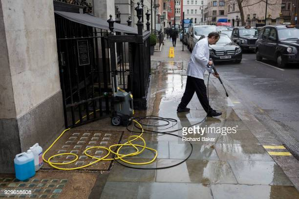 After a week of snow and ice an employee uses a pressure hose to wash down a dirty pavement at the side entrance of the Wolseley Brasserie opposite...