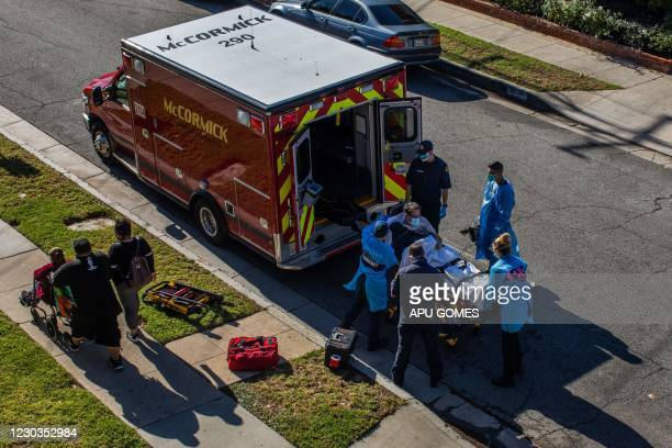 After administering him with oxygen, County of Los Angeles paramedics load a potential Covid-19 patient in the ambulance before transporting him to a...