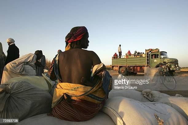 After an attack on her village forced her to flee a Chadian village woman waits for a truck to collect her belongings November 16 2006 in a village...