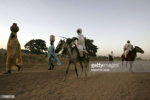 After an attack on their village forced them to flee Arab nomads on horses pass by a Chadian village woman as they came back from a water well and...