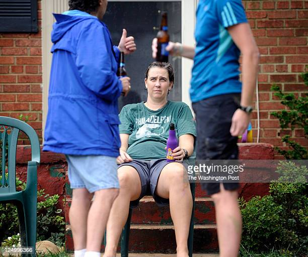 After an exhausting night and early morning of cleanup Stacy Hoeflich resident of Fenwick Drive sits with neighbors over beers outside of her flooded...