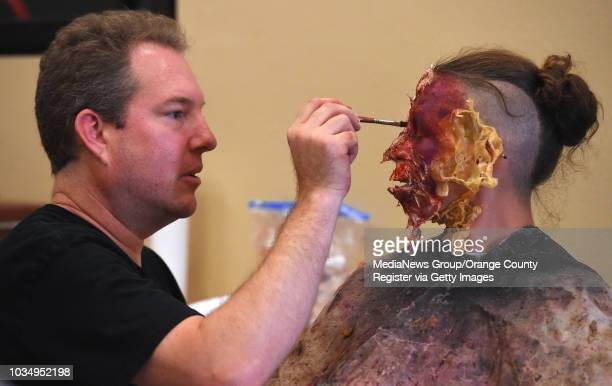 After applying cotton and latex, special effects makeup artist Brian Stock paints a zombie-like makeup to an actor named X at the Wilmington Branch...
